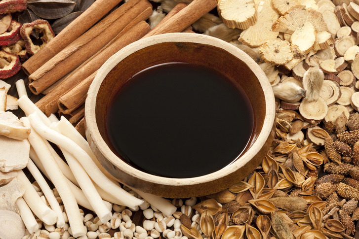 Various Chinese herbal medicine with a bowl of herbal liquid medicine