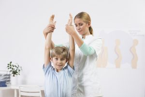 Child with scoliosis exercising and stretching with physiotherapist