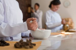 Traditional Chinese doctors mixing medicine ingredients