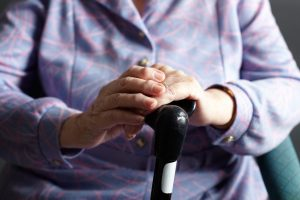 Close Up Of Senior Woman Holding Walking Stick Sitting In Chair At Home
